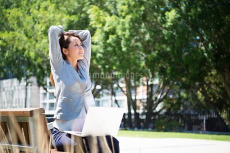 パソコンを持ってベンチでストレッチをしている女性の写真素材 [FYI01707953]