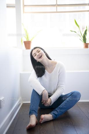フローリングの床に座って笑っている女性の写真素材 [FYI01707961]