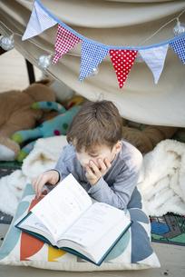 シーツで作ったテントの中で本を読んでいる男の子の写真素材 [FYI01707982]