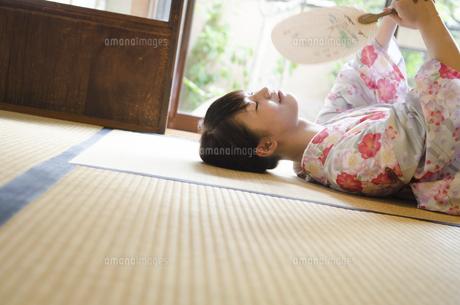 畳に寝転がってうちわで仰いでいる着物姿の女性の写真素材 [FYI01707995]