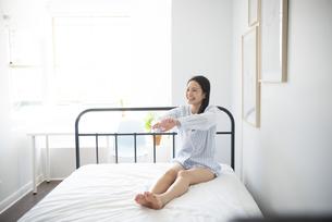 ベッドの上でストレッチしているパジャマ姿の女性の写真素材 [FYI01708020]