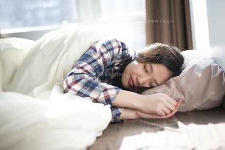 ベッドで寝ている女性の写真素材 [FYI01708032]