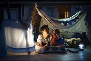 シーツで作ったテントの中で空を見上げている兄弟の写真素材 [FYI01708047]