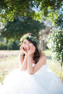 森の中で座っているウェディングドレス姿の女性の写真素材 [FYI01708054]
