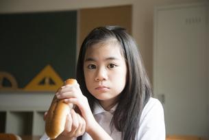 コッペパンを持っている小学生の女の子の写真素材 [FYI01708062]
