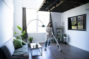 リビングで掃除機をかけている女性の写真素材 [FYI01708087]