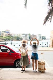 赤い車の前に立っている女性2人の後ろ姿の写真素材 [FYI01708106]