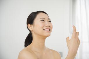 顔にスプレーをしているすっぴんの女性の写真素材 [FYI01708107]