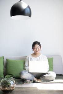 ソファに座ってパソコンを操作しながら笑っている女性の写真素材 [FYI01708167]
