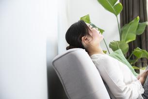 ソファに座って目を閉じている女性の写真素材 [FYI01708174]