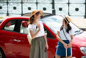 赤い車の前に立って笑っている女性2人の写真素材 [FYI01708177]