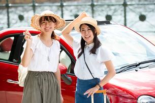 赤い車の前に立って笑っている女性2人の写真素材 [FYI01708183]