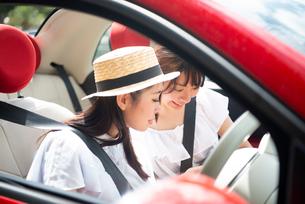 車の中でスマホを見ている女性2人の写真素材 [FYI01708185]