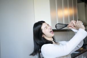 キッチンで泡立て器を持って歌っている女性の写真素材 [FYI01708200]