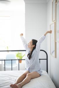 ベッドの上でストレッチしているパジャマ姿の女性の写真素材 [FYI01708221]