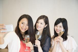 シャンパンを持って自撮りをしている女性たちの写真素材 [FYI01708244]