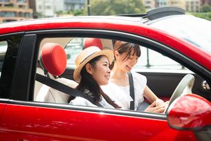 車の中でスマホを見ている女性2人の写真素材 [FYI01708284]
