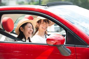 赤い車に乗って笑っている女性2人の写真素材 [FYI01708315]