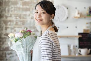 花束を持っている笑顔の店員の女性の写真素材 [FYI01708346]