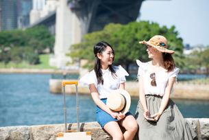水辺をバックに笑っている女性2人の写真素材 [FYI01708361]