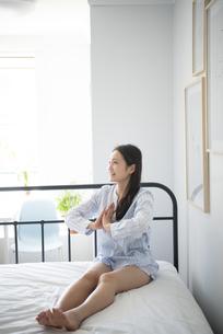ベッドの上でストレッチしているパジャマ姿の女性の写真素材 [FYI01708379]