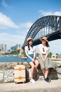 橋をバックに笑っている女性2人の写真素材 [FYI01708392]