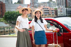 赤い車の前に立って笑っている女性2人の写真素材 [FYI01708398]