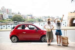 赤い車の前に立っている女性2人の後ろ姿の写真素材 [FYI01708417]