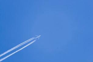 真っ青な空を飛ぶ飛行機と雲の写真素材 [FYI01708427]