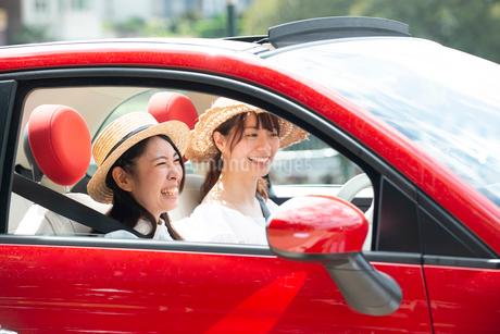 赤い車に乗って笑っている女性2人の写真素材 [FYI01708428]