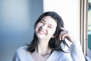 白いニットを着て笑っている女性の写真素材 [FYI01708452]