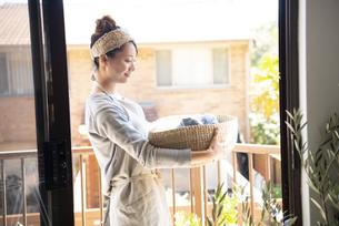 洗濯物の入ったかごを持っている女性の写真素材 [FYI01708469]