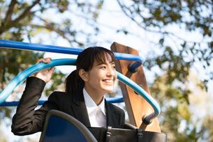 滑り台の上で笑っているスーツ姿の女性の写真素材 [FYI01708495]