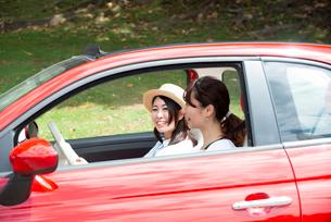 赤い車に乗って笑っている女性2人の写真素材 [FYI01708508]