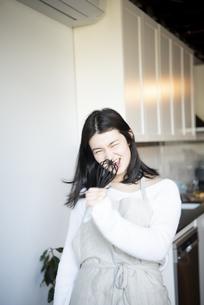 キッチンで泡立て器を持って歌っている女性の写真素材 [FYI01708515]