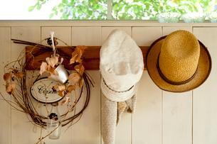 かべに掛かったリースと帽子の写真素材 [FYI01708585]