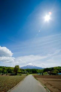 太陽と青空と富士山に続く一本道の写真素材 [FYI01708658]