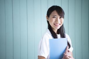 ノートを抱えて笑っている働く女性の写真素材 [FYI01708728]