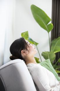 ソファに座って目を閉じている女性の写真素材 [FYI01708781]