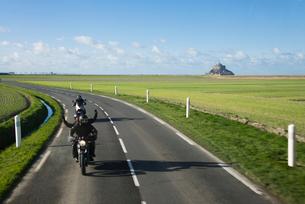 遥か遠くにモンサンミッシェルを望む田園地帯を走るバイクの写真素材 [FYI01708867]