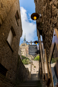 建物の間から見るモンサンミッシェル修道院の尖塔の写真素材 [FYI01708869]
