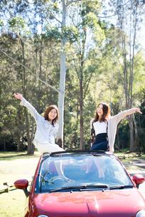 車に座ってポーズをしている女性2人の写真素材 [FYI01708933]