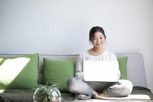 ソファに座ってパソコンを操作しながら笑っている女性の写真素材 [FYI01709012]