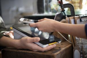 お店でスマホを使って電子決済をしている女性の手元の写真素材 [FYI01709042]