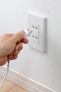 電気コードを持つ手とコンセントの写真素材 [FYI01709168]