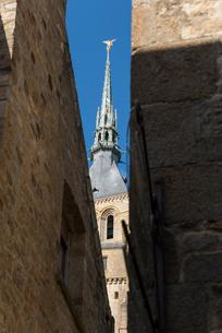 建物の間から見るモンサンミッシェル修道院の尖塔の写真素材 [FYI01709287]
