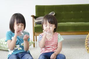 風船を膨らませている男の子と女の子の写真素材 [FYI01709304]