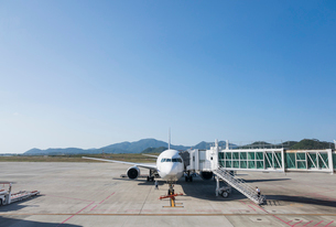 遠くに山並みを見る駐機中の飛行機の写真素材 [FYI01709734]