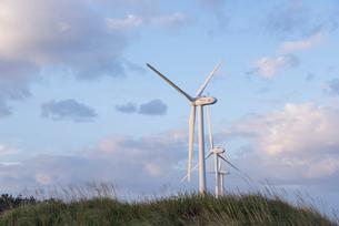 土手に立ち並ぶ風力発電塔の写真素材 [FYI01709835]