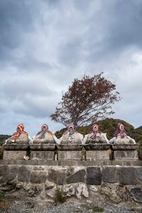 暗雲立ちこめる中頭巾を被るお地蔵さんが並ぶ恐山風景の写真素材 [FYI01709857]